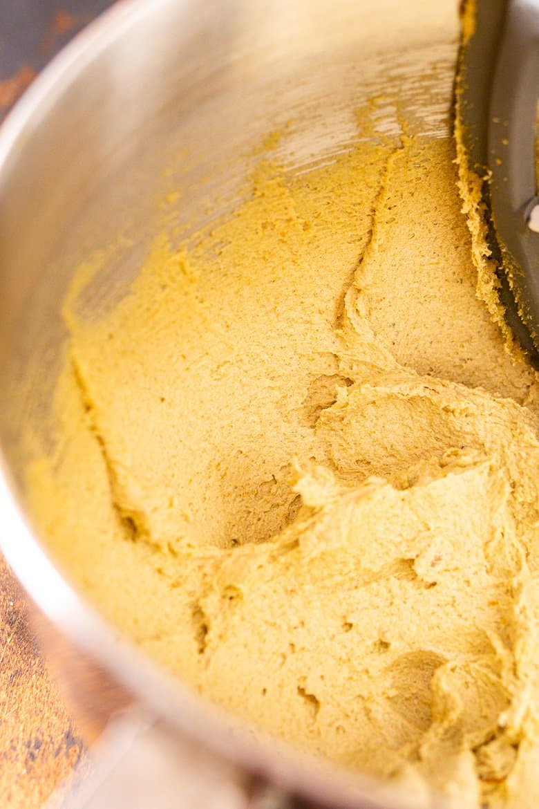 Beating the cookie dough until it's light and fluffy in a mixing bowl.