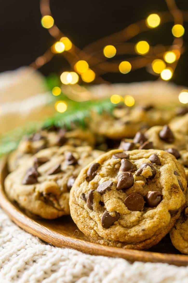 A close-up view of a spiced holiday chocolate chip cookies with lights in the background.