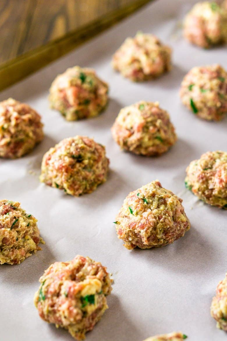 The Italian meatballs shaped onto parchment paper-lined baking sheet.