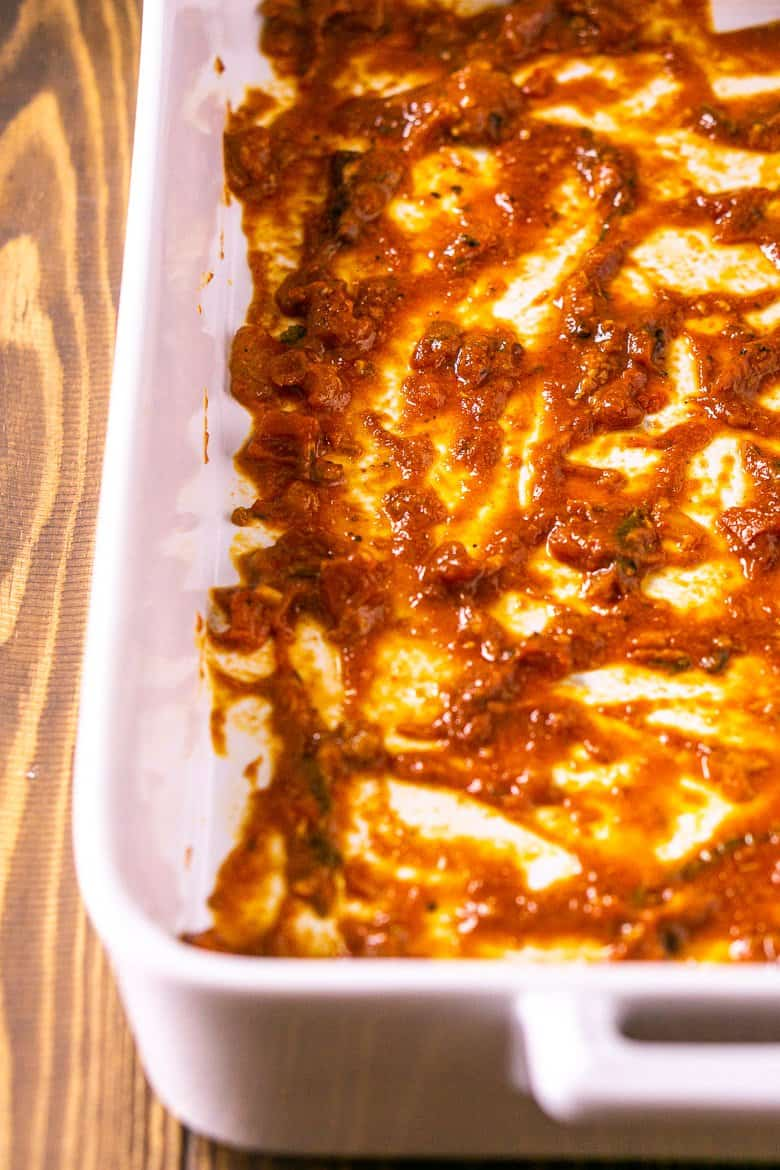 A white lasagna pan with a layer of sauce on the bottom.