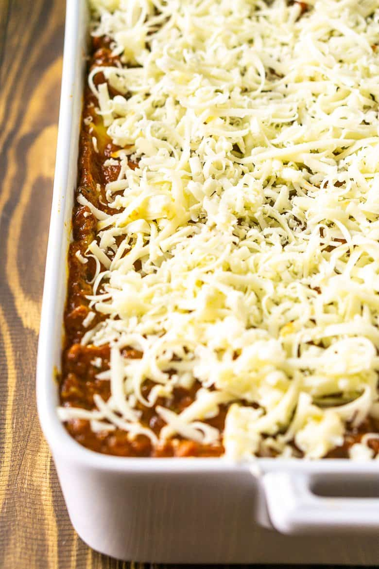 Layering the meatball lasagna in a baking dish and finishing with shredded mozzarella.