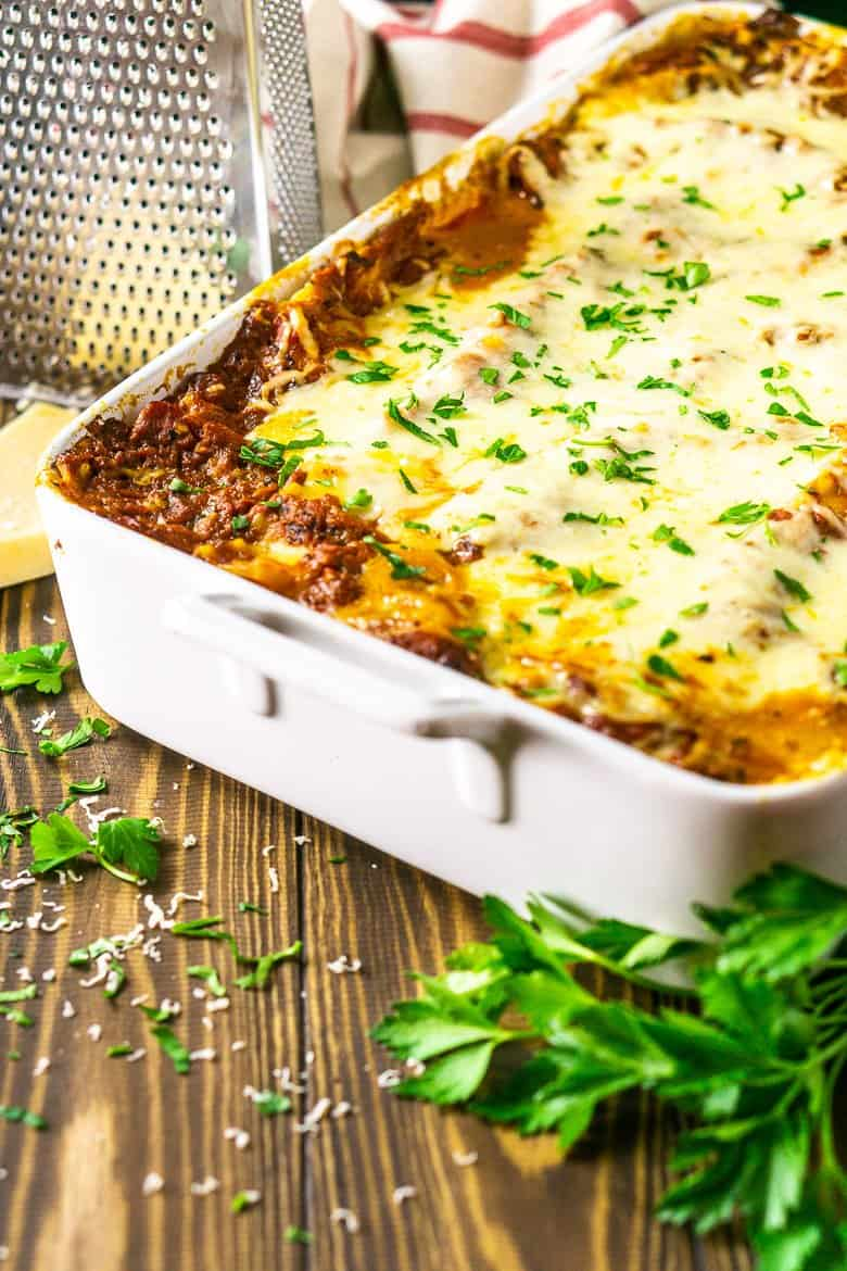 A pan of meatball lasagna with fresh parsley and a cheese grate with a slab of Parmesan.