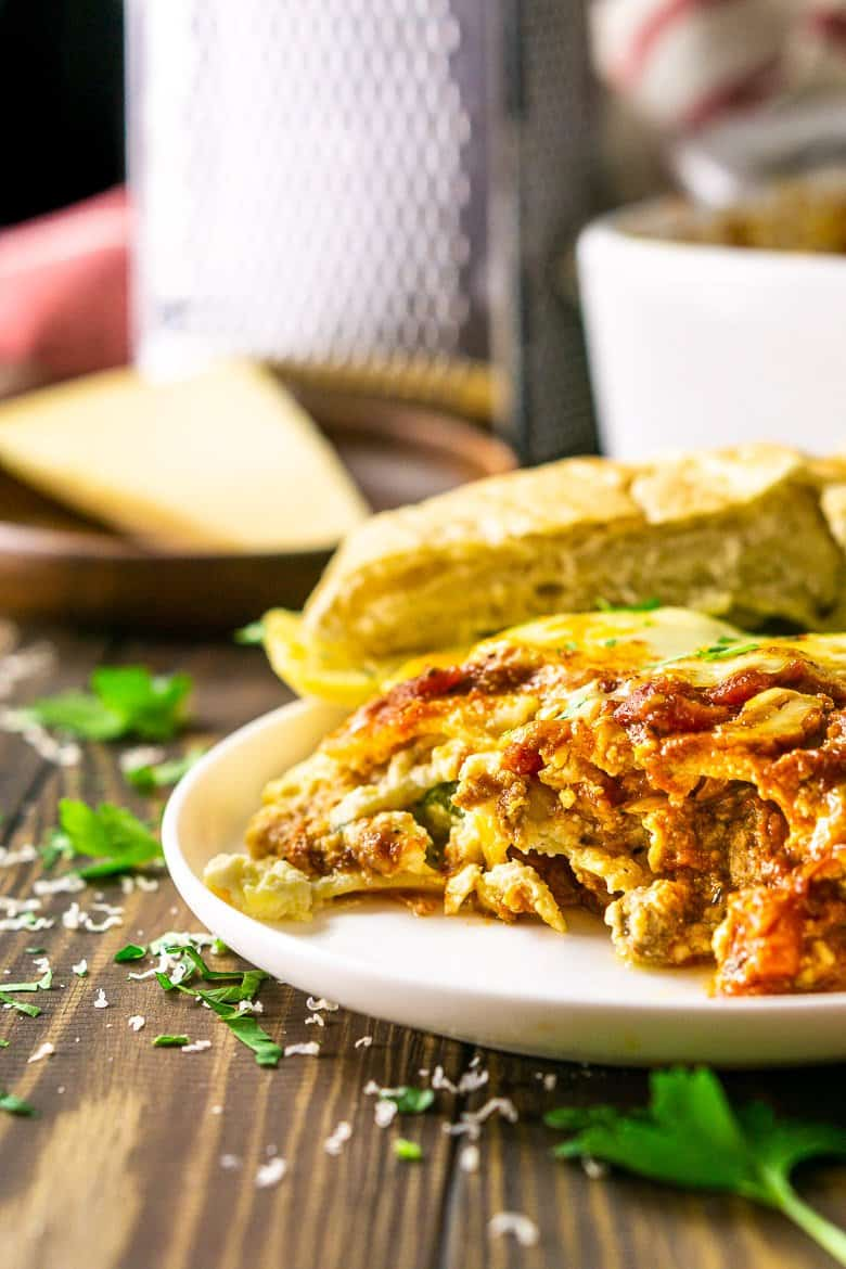 A slice of meatball lasagna with the cheese grater and pan of lasagna in the background.