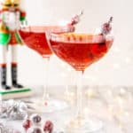 Two Sugar Plum Fairy Martinis on a marble board with a nutcracker and lights behind them.