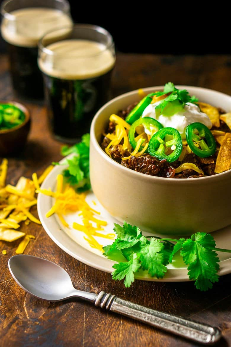 Texas chili in a bowl with a spoon on the side and a bowl of sliced jalapenos.