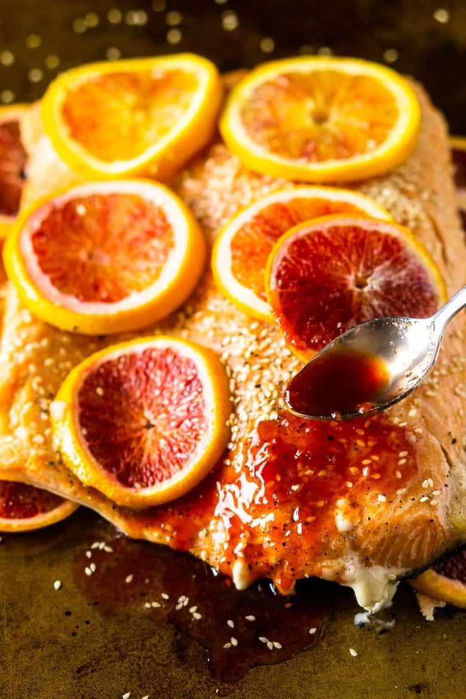 Spooning the blood orange glaze onto the slab of salmon.