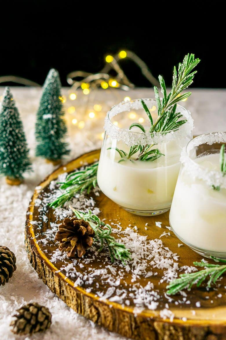 Two Winter Wonderland Margaritas on a wooden board with pinecones, fake trees and lights around them.