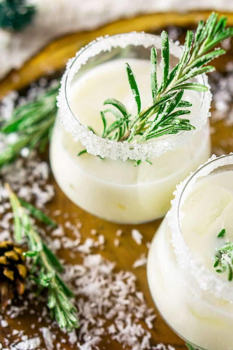 A close-up of an aerial shot of the winter coconut margaritas with candied rosemary.