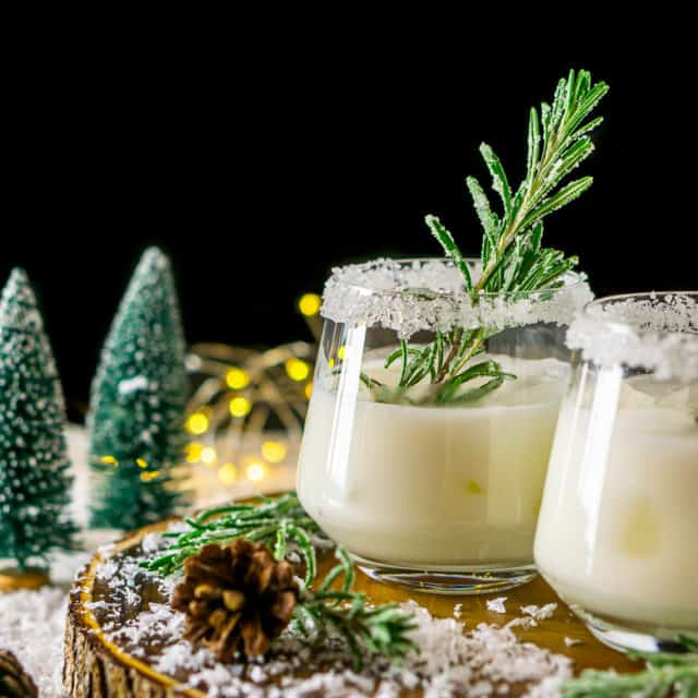A Winter Wonderland Margarita on a wood board with candied rosemary and fake trees and lights in the background.