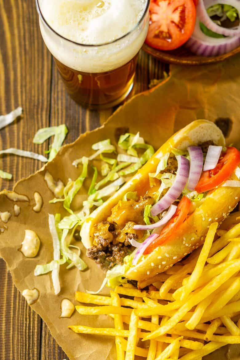 An aerial view of the cheeseburger sub with a plate of toppings and shredded lettuce scattered around it.