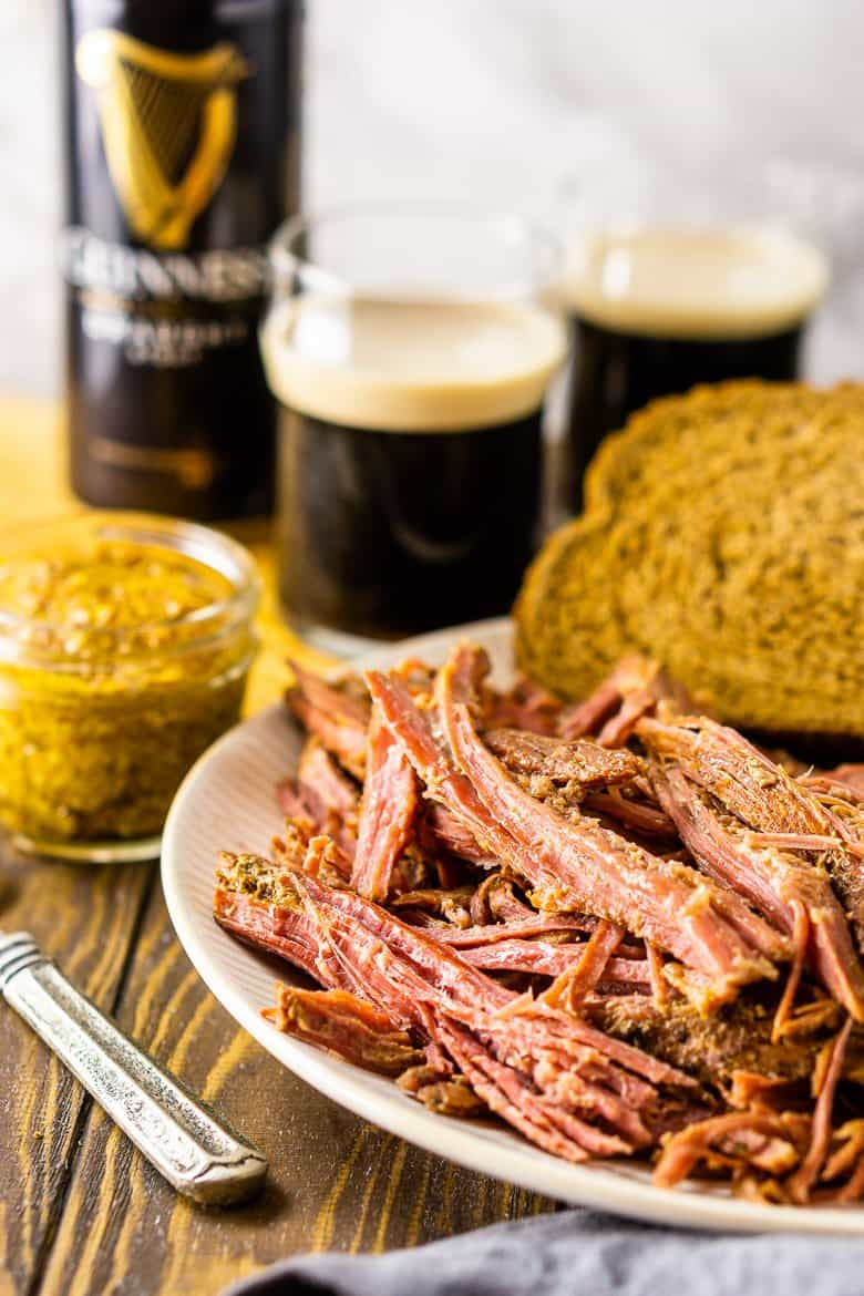 A plate of slow cooker Guinness corned beef with rye bread and mustard and two beers in the background.