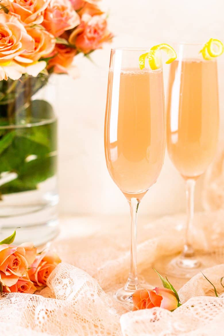 Two sparkling rosé French 75 cocktails with a vase of roses, roses on the ground and pink lace.