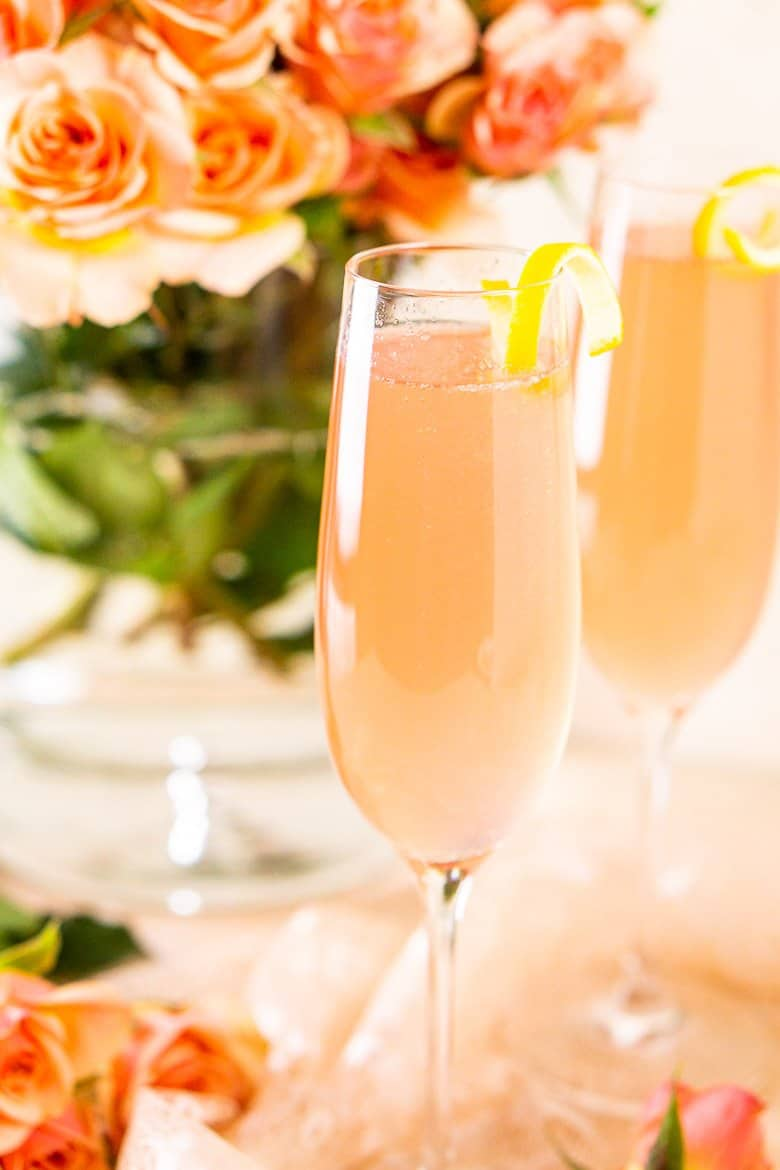 A close-up view of a sparkling rosé French 75 with a lemon twist and another cocktail in the background.