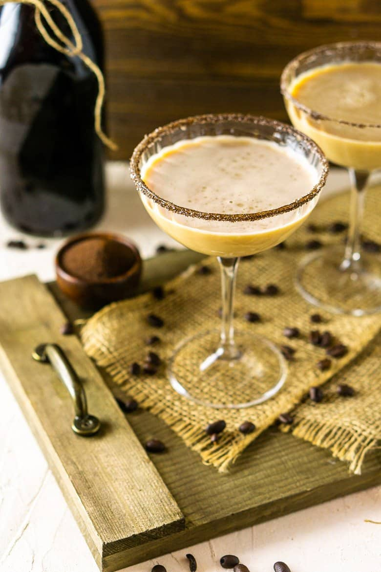 Two Irish coffee martinis on a wooden platter.