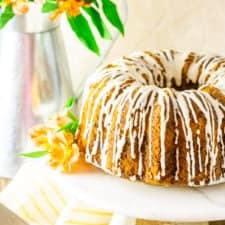 The carrot pound cake with a cream cheese glaze on a marble cake stand with orange flowers.