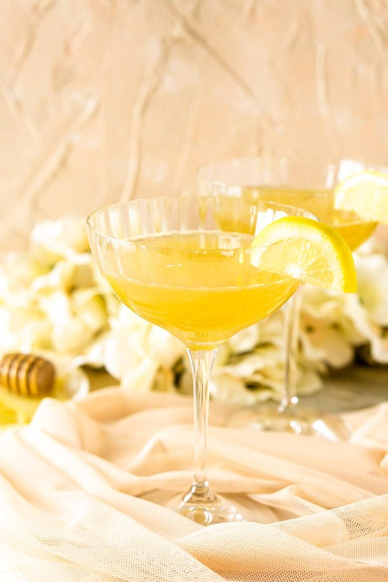A close-up view of one gin bee's knees with flowers and a plate of honey.