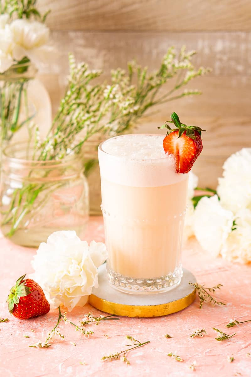 A strawberry-rhubarb gin fizz on a marble coaster with white flowers surrounding it.