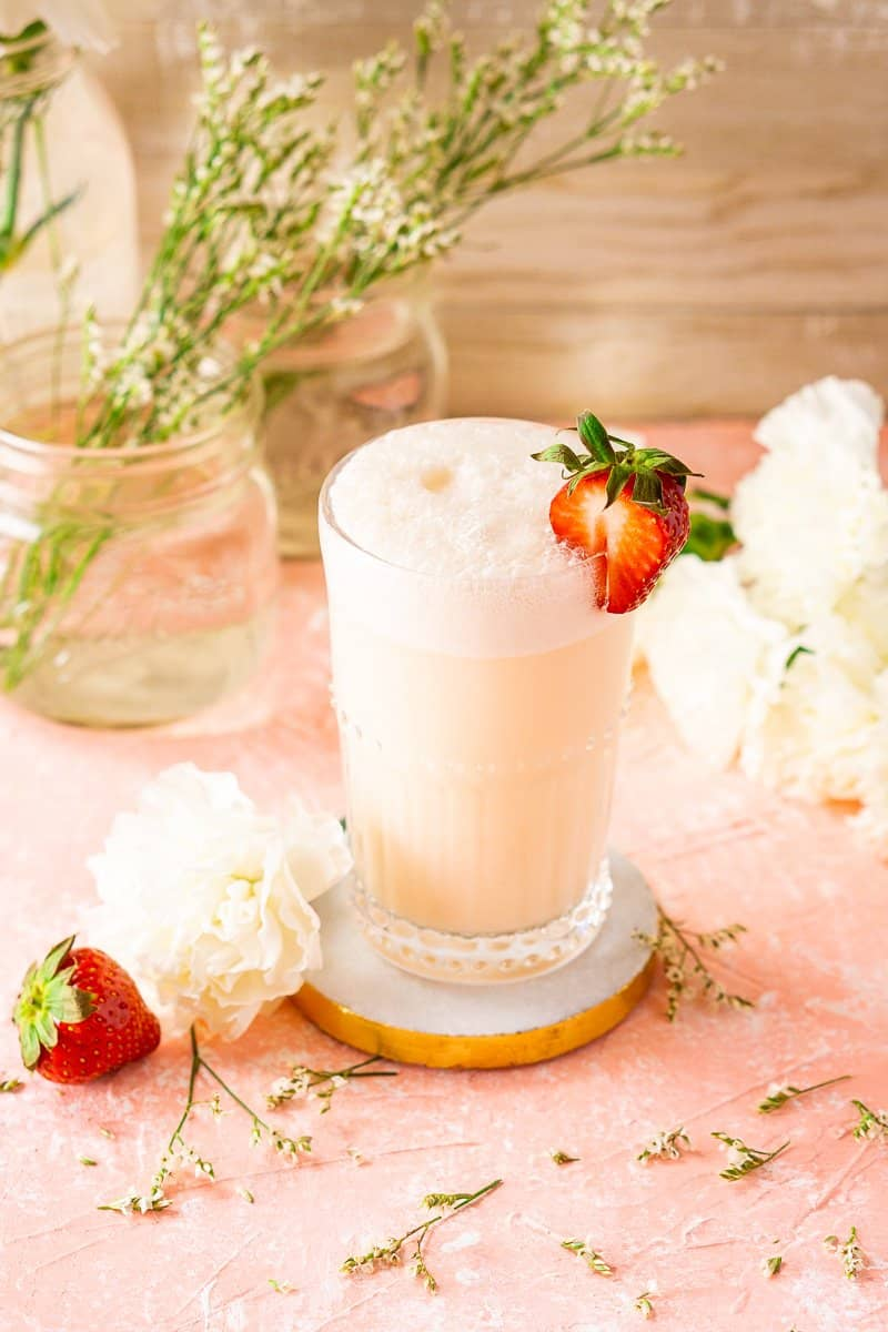 An aerial view of a strawberry-rhubarb gin fizz with flowers and a strawberry.