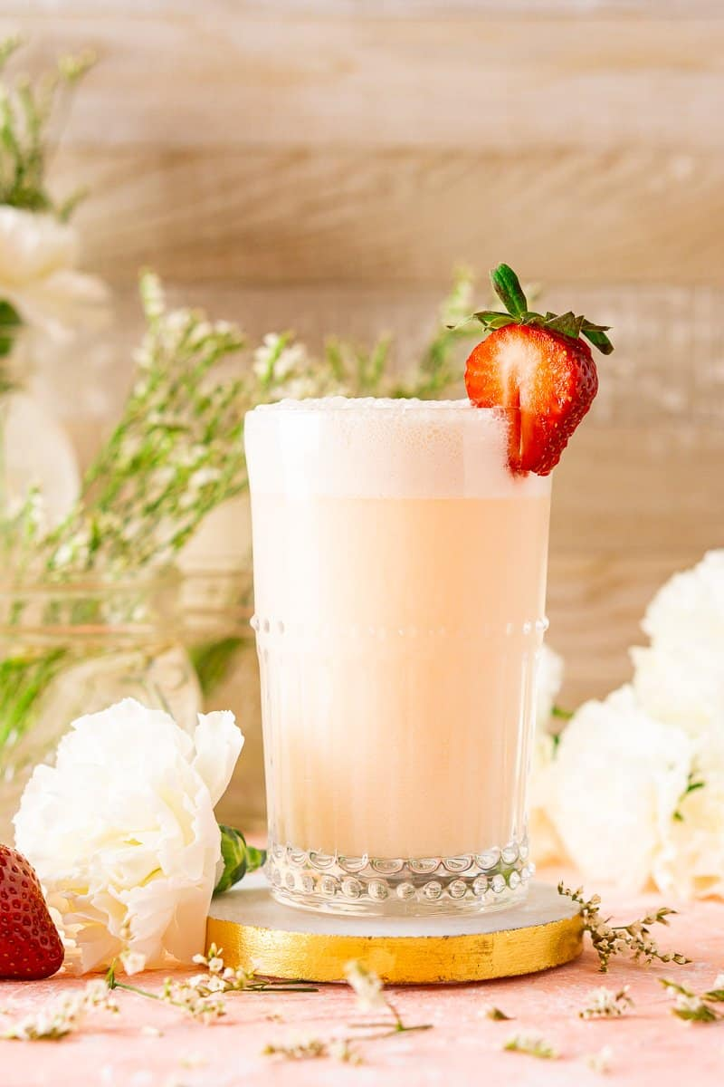 Looking up at the strawberry-rhubarb gin fizz on a marble coaster with a strawberry to the side.