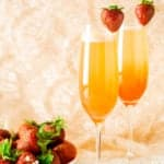 Two honeyed strawberry-rhubarb mimosas with a plate of strawberries on the side.