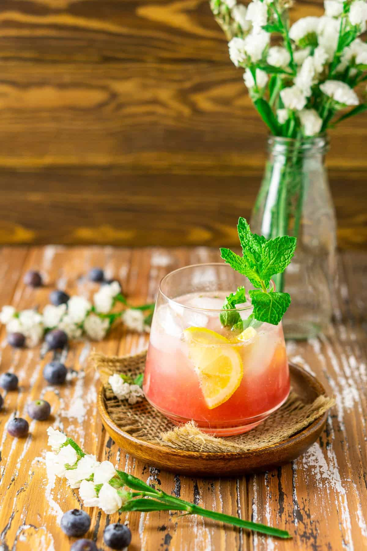 Looking down at a blueberry bourbon smash on a wooden background.