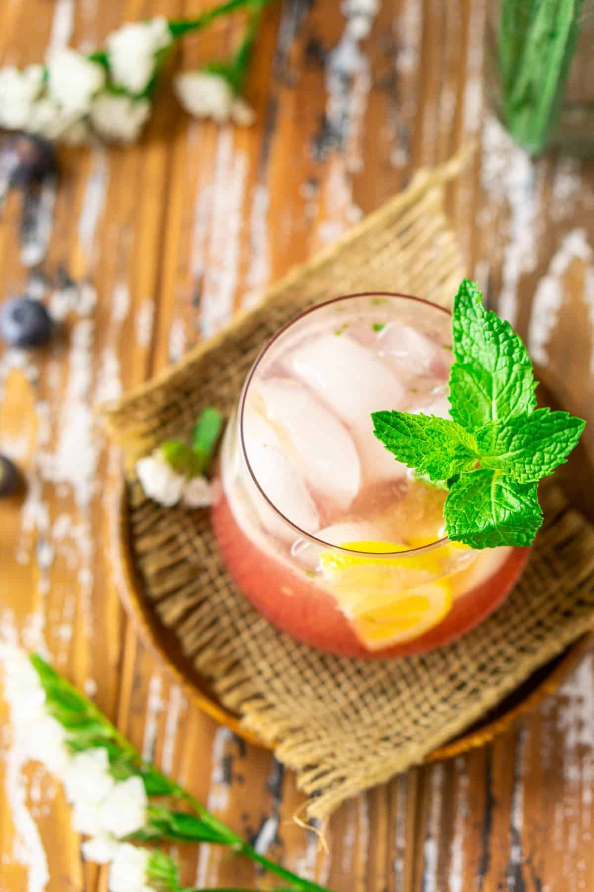 An aerial view of the blueberry bourbon smash with a sprig of mint on a wooden plate.