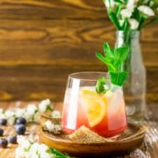 A blueberry bourbon smash on a wooden plate with white flowers in the background.
