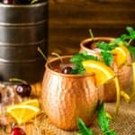 A cherry-orange Kentucky mule on burlap with cherries and orange slices around it.