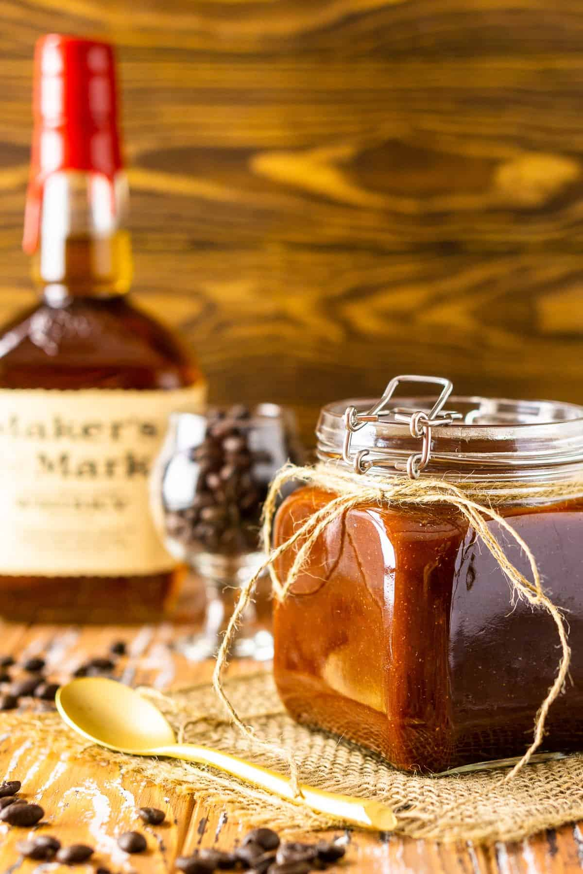 A jar of coffee-bourbon BBQ sauce with a bottle of Maker's Mark and glass of coffee beans in the background.