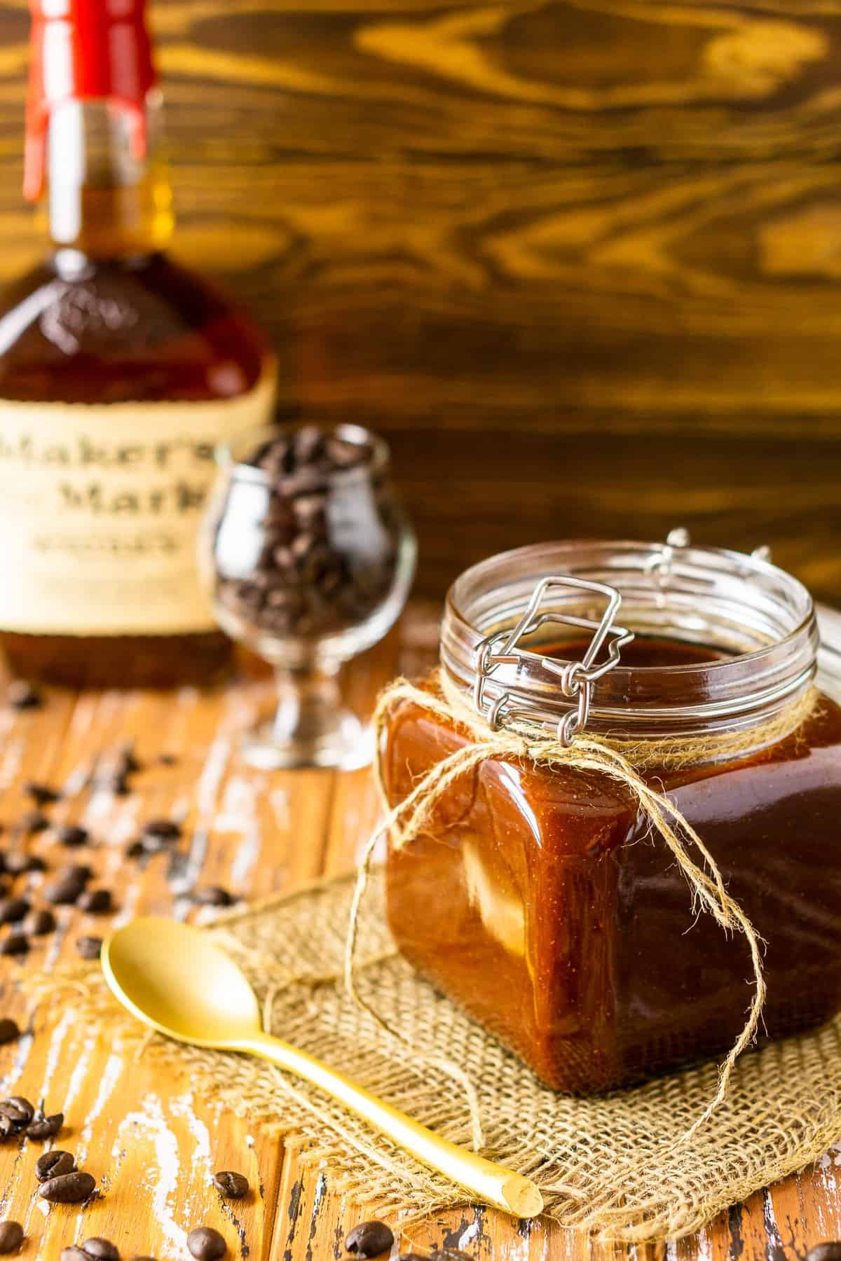 A jar of coffee-bourbon BBQ sauce on burlap with coffee beans around it.