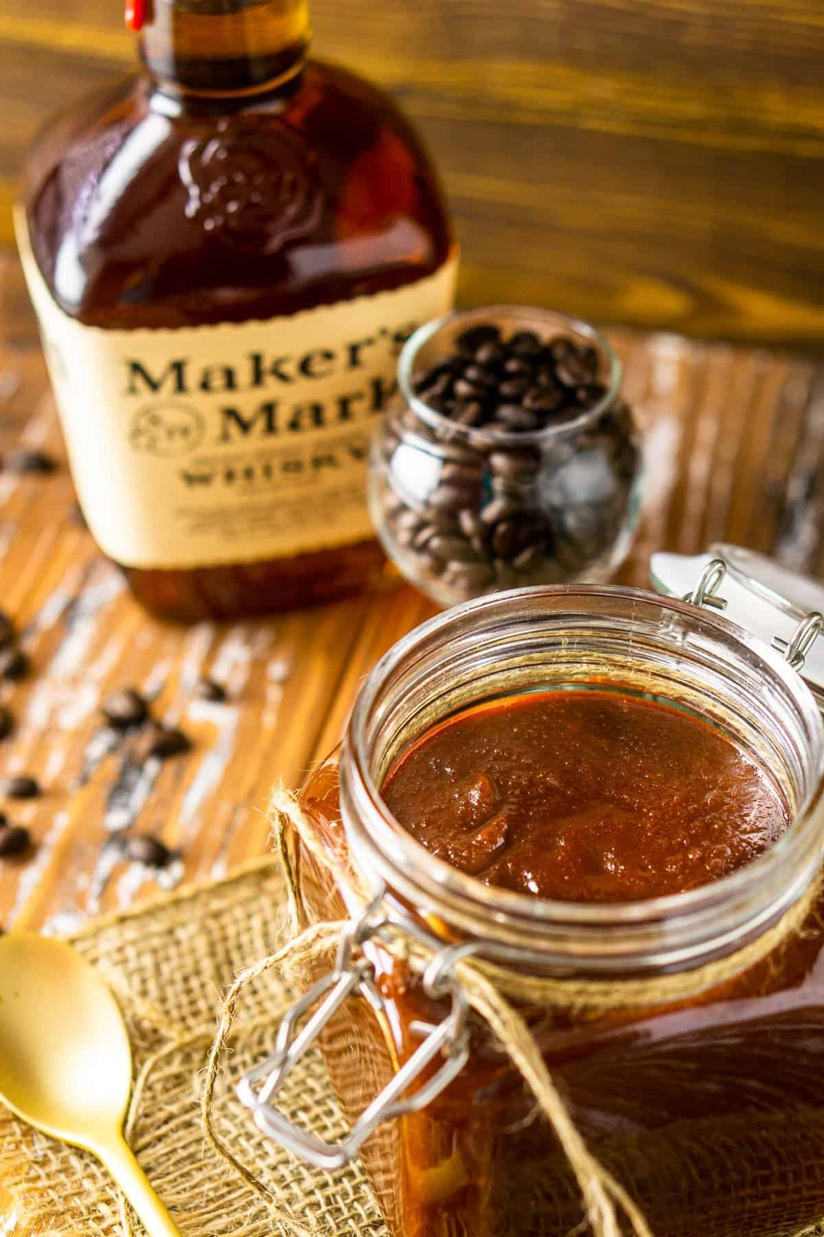 A close-up of the jar of coffee-bourbon BBQ sauce with a bottle of bourbon.
