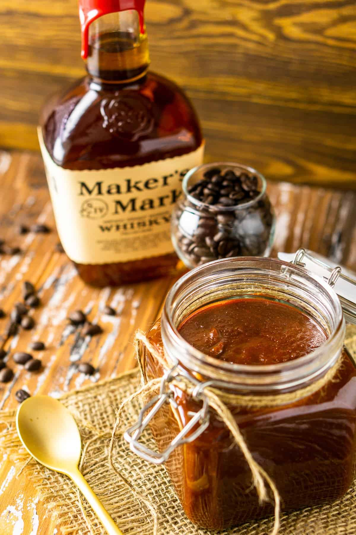 Looking down at the coffee-bourbon BBQ sauce on burlap with a gold spoon to the side.
