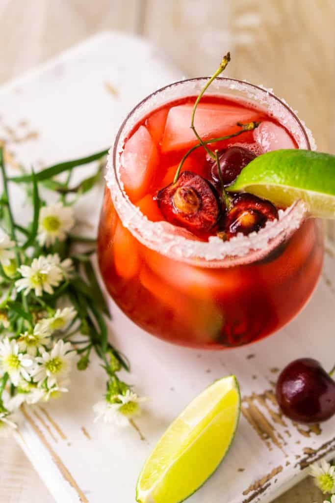 An aerial view of the cherry margarita with garnishes on the side on a white wooden board.