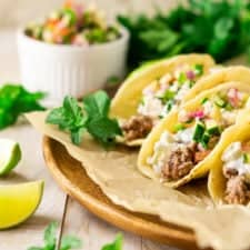 Three Greek lamb tacos on a wooden plate with cucumber pico de gallo, herb and lime slices on the side.