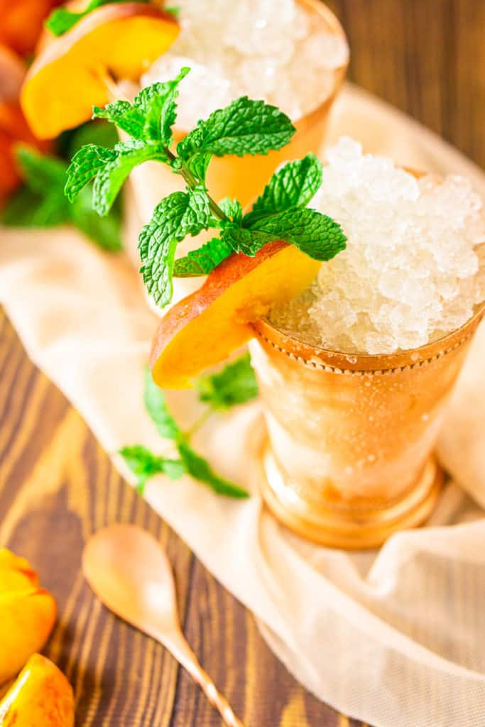 An aerial view of two brown sugar-peach mint juleps with a bar spoon on the side.