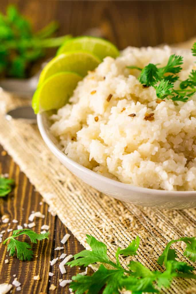 The coconut-lime rice in a white bowl on a placemat with lime slices.