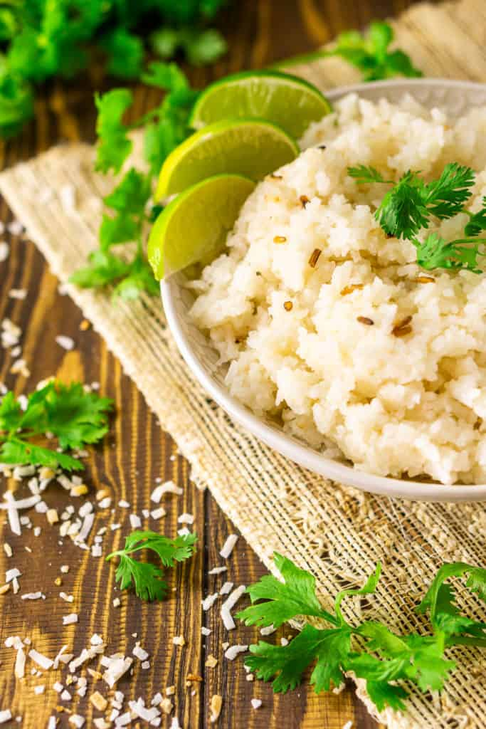 A bowl of tropical coconut-lime rice on a placemat with toasted coconut and cilantro around it and two spoons in the background.