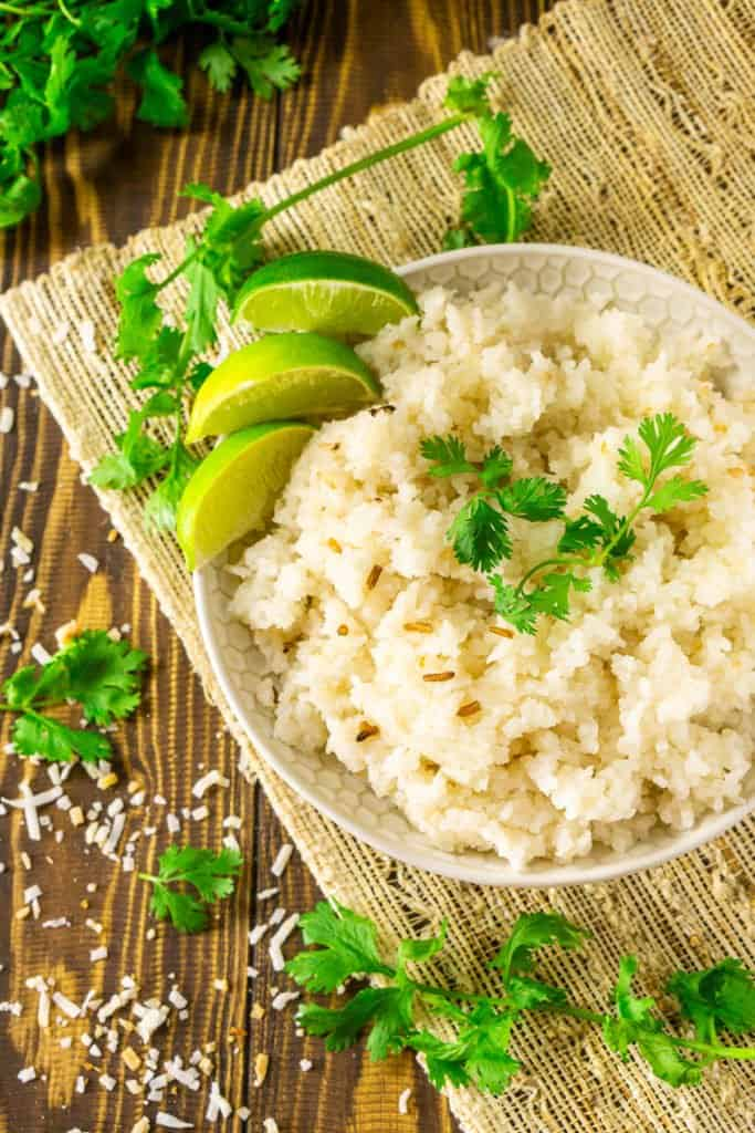 An aerial view of a the coconut-lime rice with a cilantro bunch and toasted coconut around it.