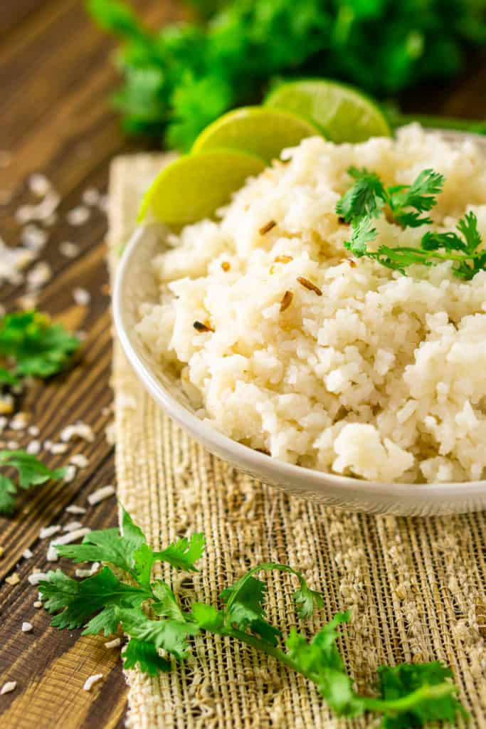 A bowl of coconut-lime rice with a sprig of cilantro framing it on a placemat.