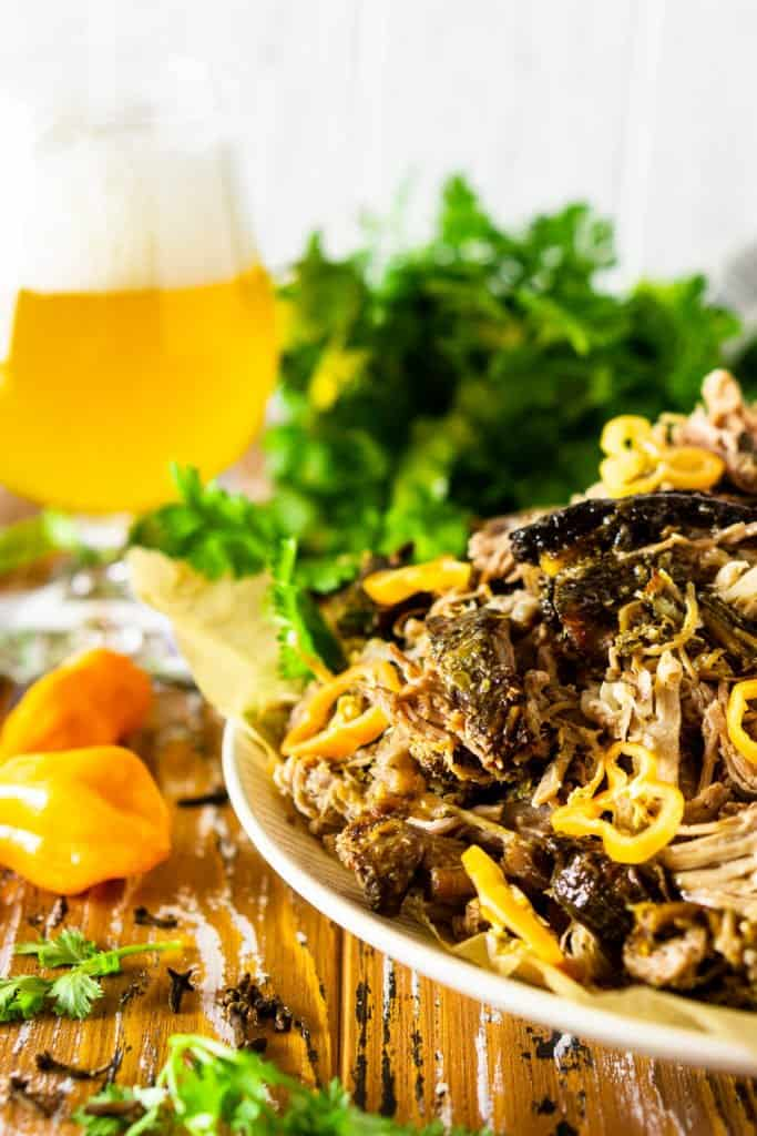 A plate of jerk pork shoulder with a beer and a bunch of fresh cilantro.