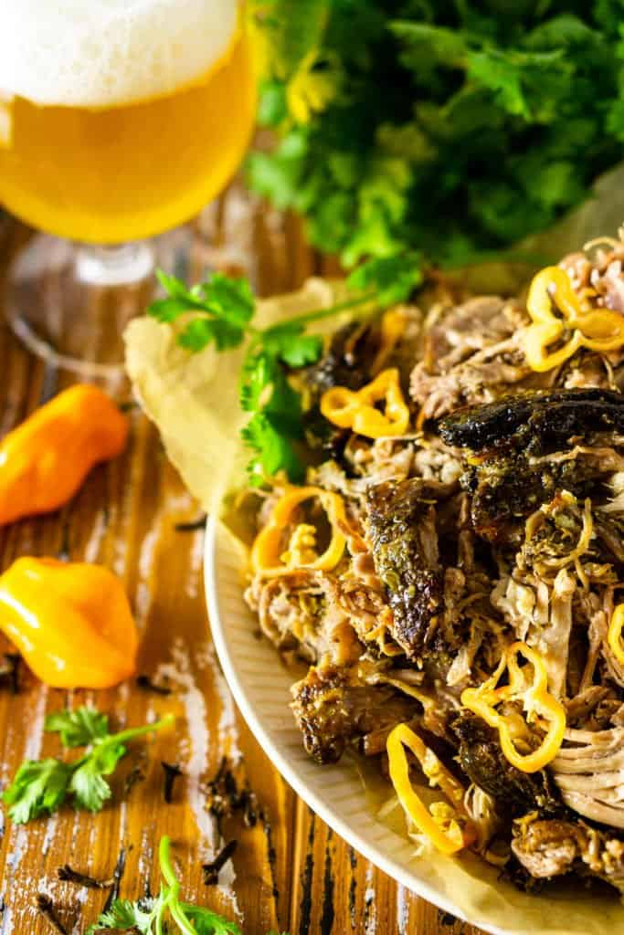 A pile of shredded Jamaican jerk pork shoulder on a plate with a beer, cilantro, and habanero peppers on the side.