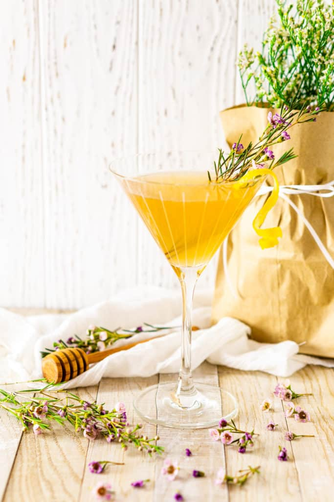 The lavender bee's knees with a vase of flowers and purple flower buds on the ground.