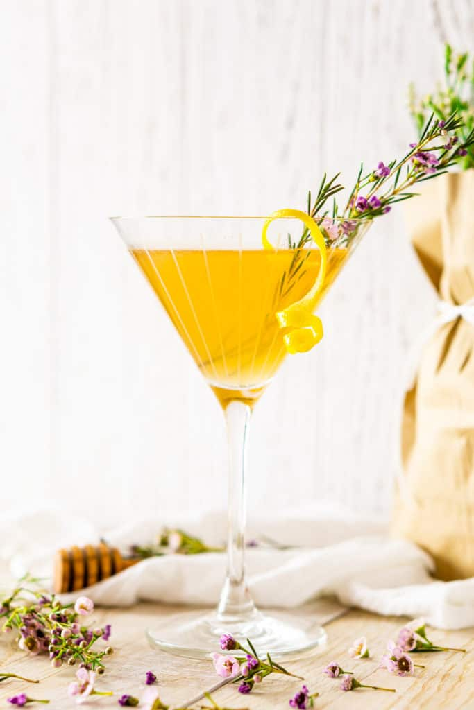 Looking straight on to the lavender bee's knees cocktail with a bundle of flowers in the background.