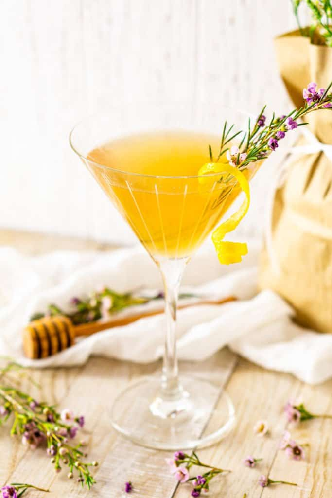 The lavender gin cocktail with a lemon twist and flowers around it.