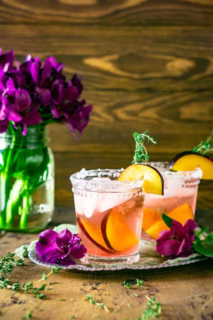 Two plum-thyme margaritas with the flower vase to the side.