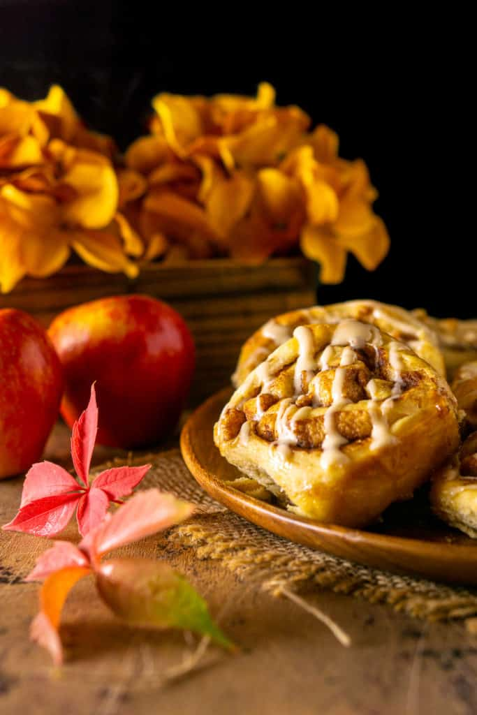 A plate of apple cinnamon rolls with fall flowers in the background.
