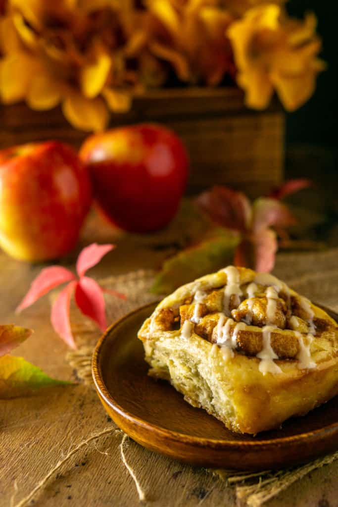 A single apple cinnamon roll on a wooden plate with fall leaves, apples and flowers in the background.