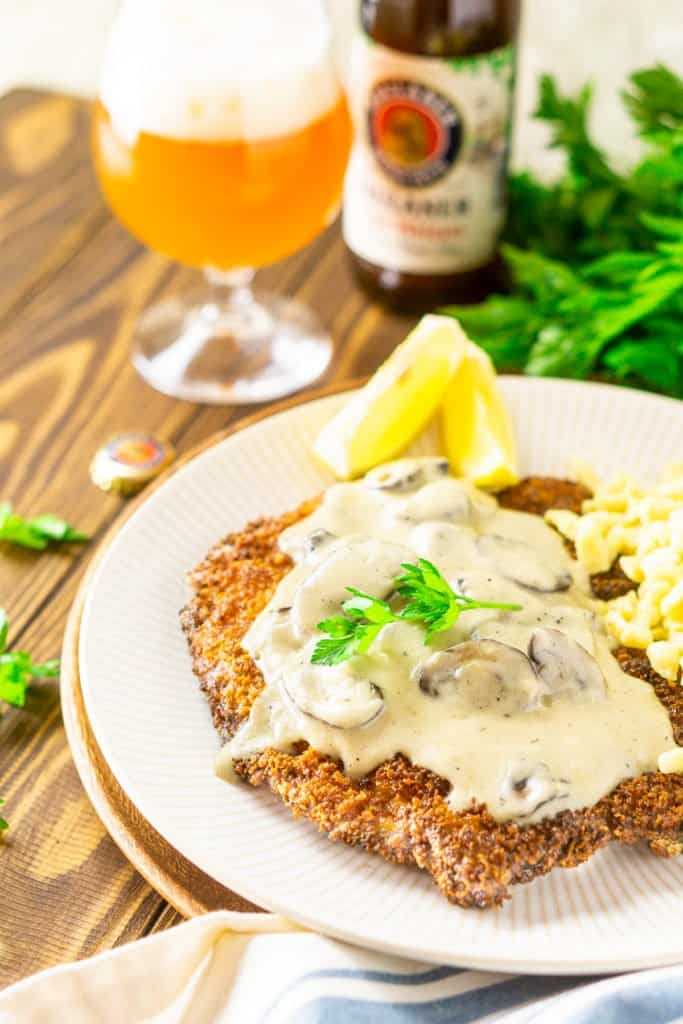 A side shot of the beer-brined schnitzel with mushroom gravy and a beer in the background.