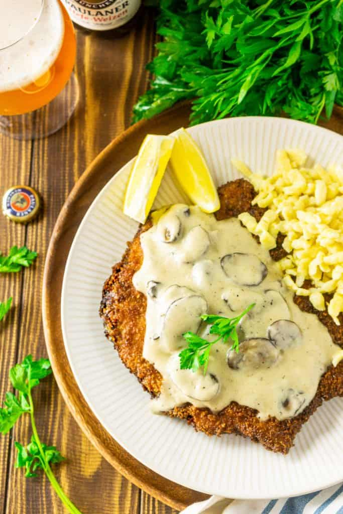 An aerial view of the beer-brined schnitzel with spaetzle on the side with fresh parsley.