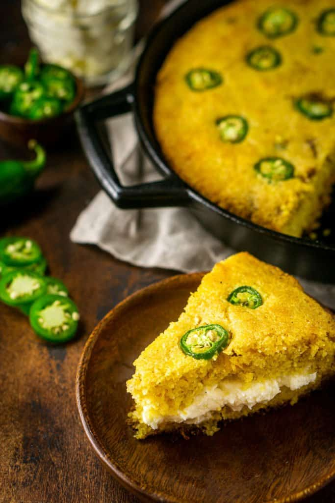 Looking down on a slice of jalapeno popper cornbread filled with the whipped cream cheese butter with a skillet of cornbread behind the slice and jalapenos on the side.